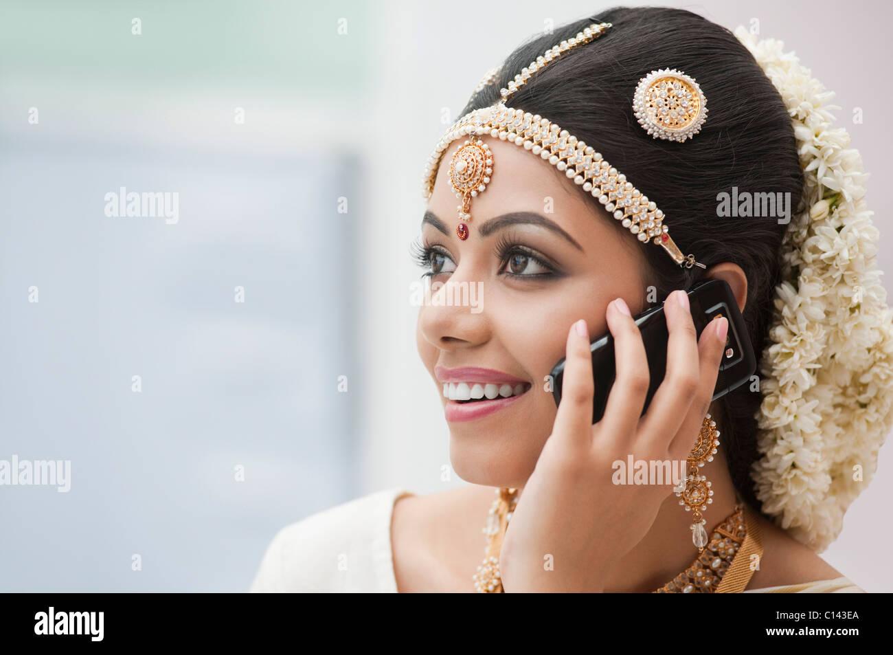 Novia vestidos tradicionales del sur de la India hablando por un teléfono móvil Imagen De Stock