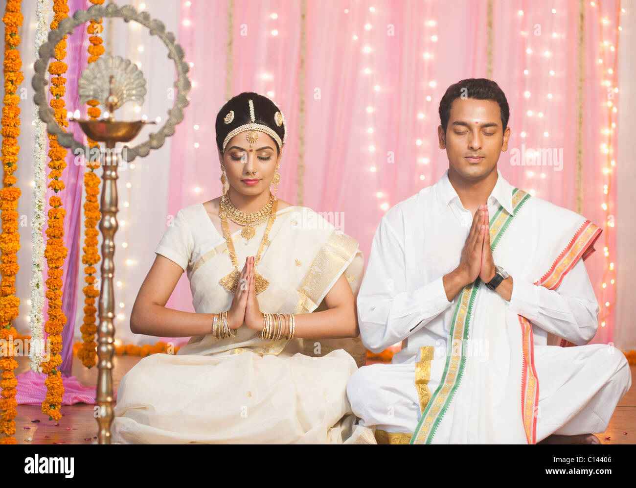La novia y el novio en traje tradicional del sur de India orando en ...