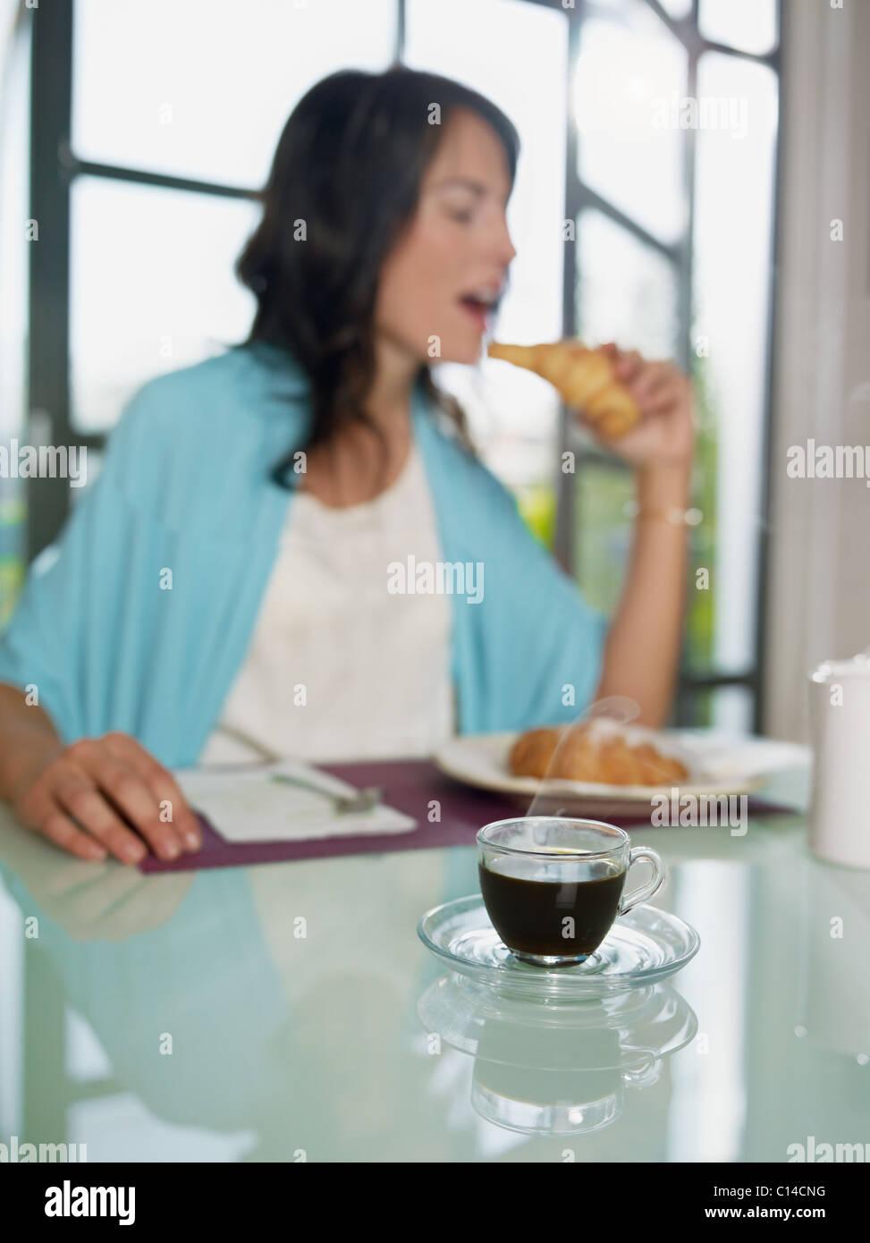 Mujer adulta media comiendo croissants en casa. De forma vertical, copie el espacio, centrarse en la taza de café Foto de stock