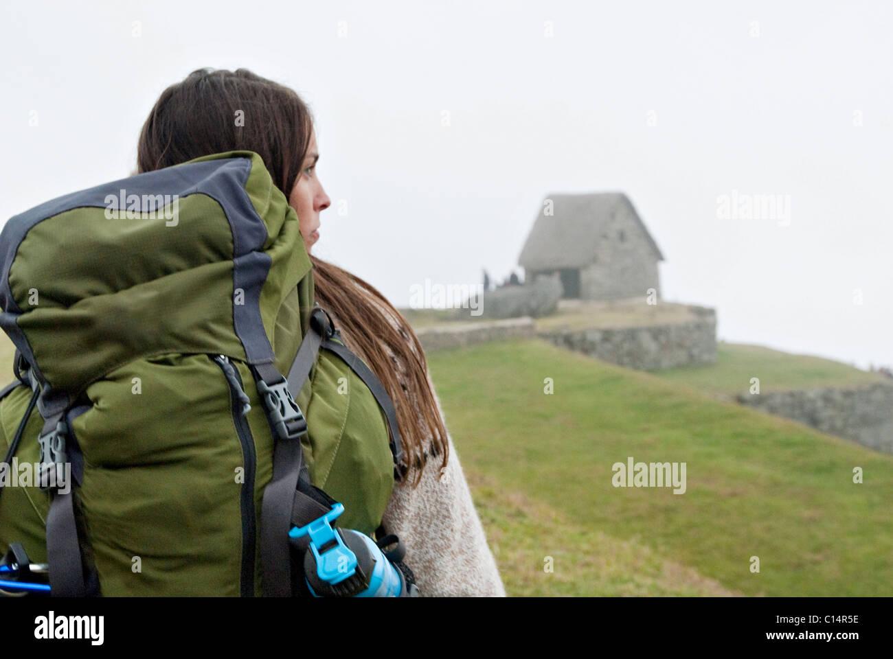 Una joven mujer caminatas hacia las ruinas de Machu Picchu en una niebla por la mañana. Foto de stock