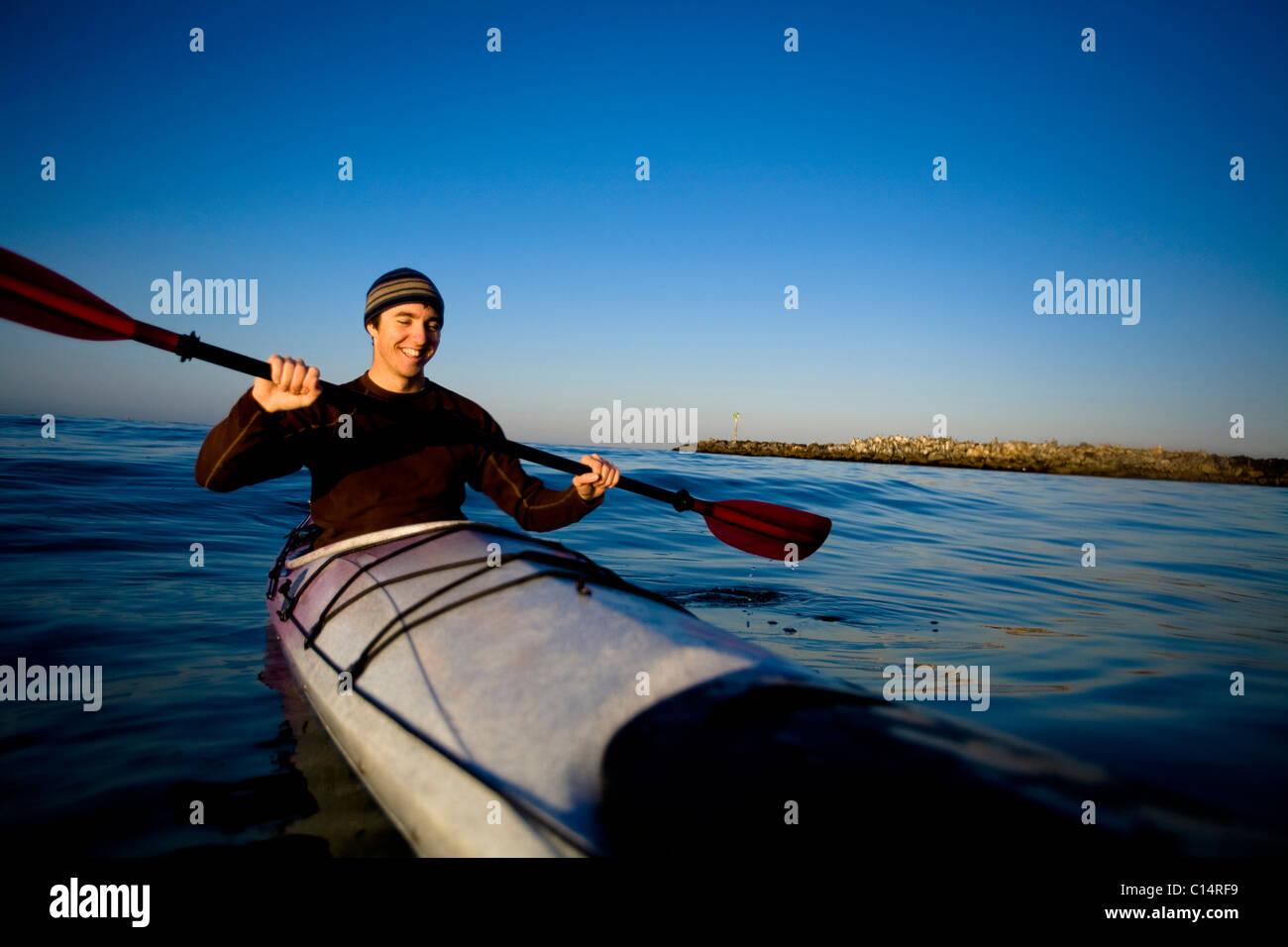 Un hombre joven sonríe mientras remando un kayak de travesía, justo en las afueras de Ventura Harbor en Imagen De Stock