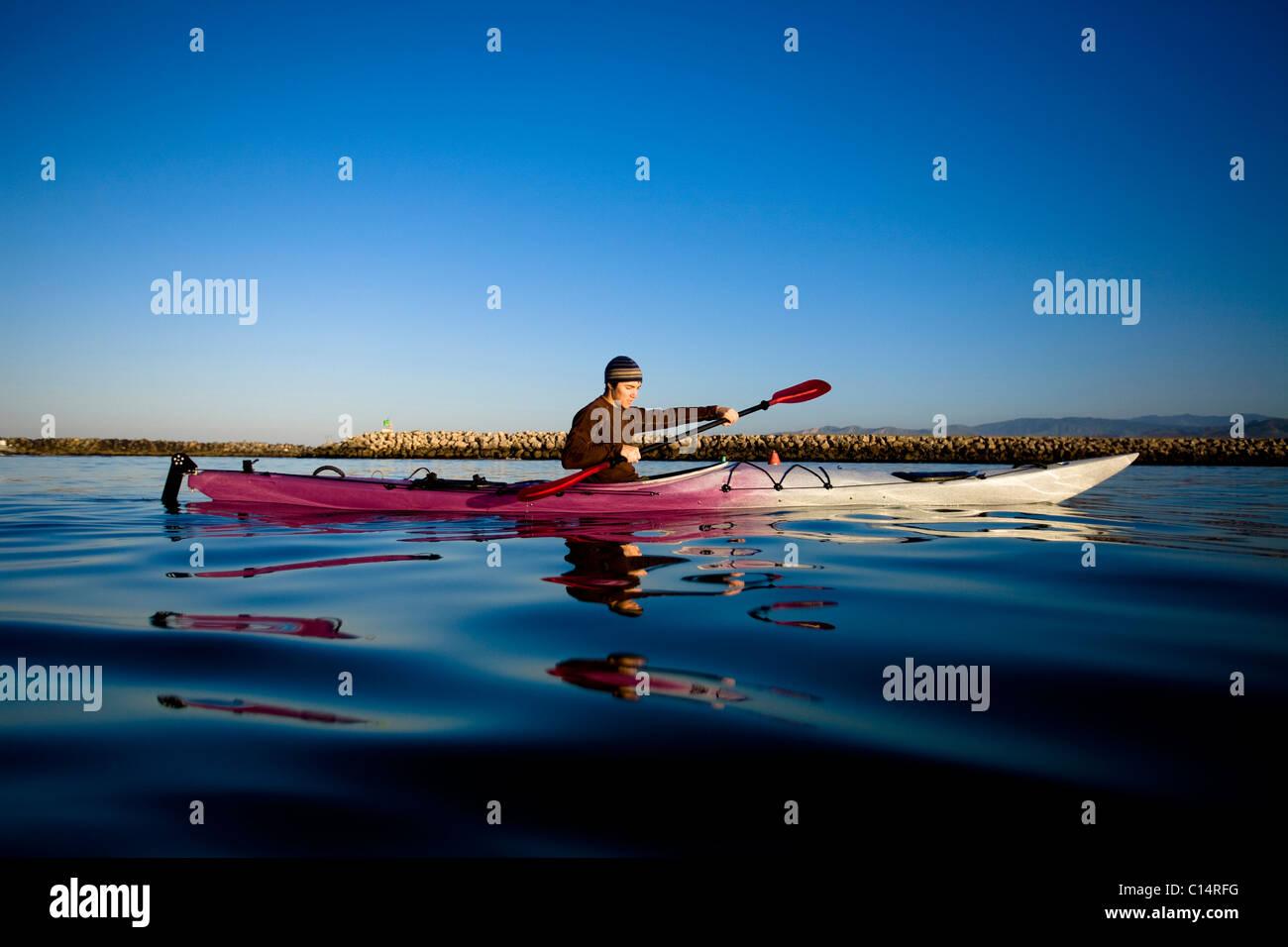 Un joven mira a su reflejo mientras remando un kayak de travesía, justo en las afueras de Ventura Harbor en Imagen De Stock