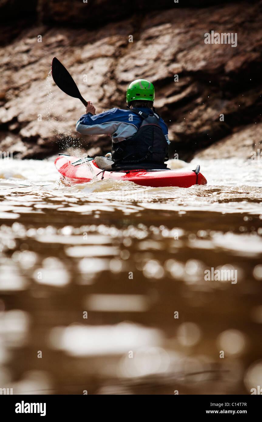 Un hombre de mediana edad palas su kayak por aguas bravas en el río Salt en Arizona. Imagen De Stock