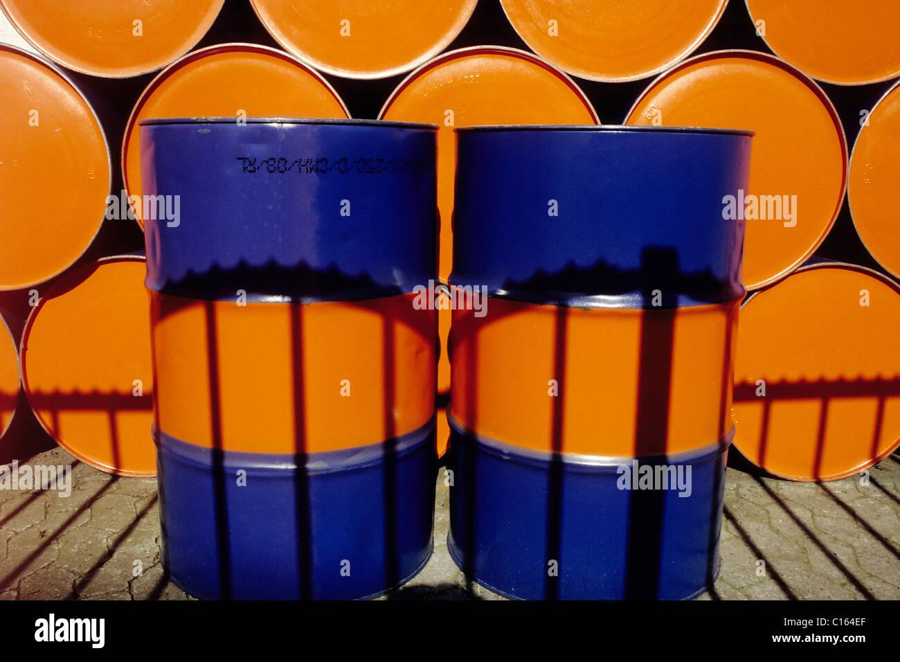 Dos bidones de aceite vertical pintado de dos colores de pie en frente de una fila de tambores de aceite apiladas Imagen De Stock