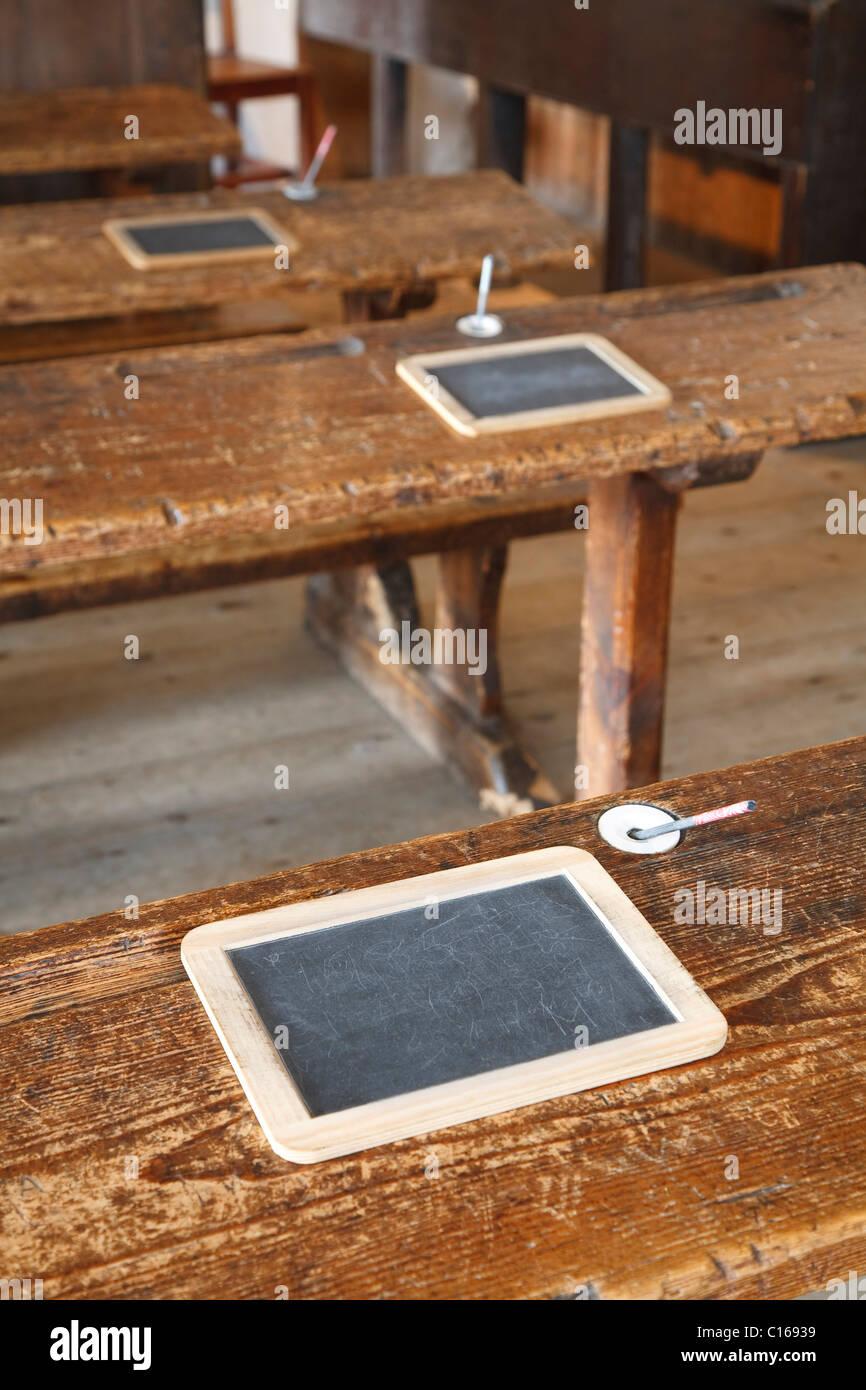 Las antiguas aulas con bancos de madera tradicional y tabletas de pizarra Foto de stock