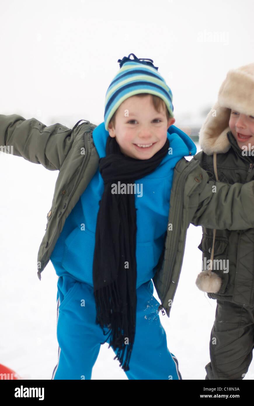 Chicos de remolque en la nieve. Foto de stock