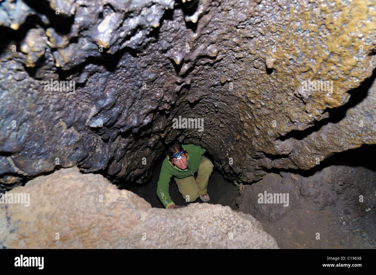 Río de lava cueva, cueva Explorer vistiendo un faro en un tubo de lava volcánica, Monumento Nacional Volcánico Newberry Foto de stock
