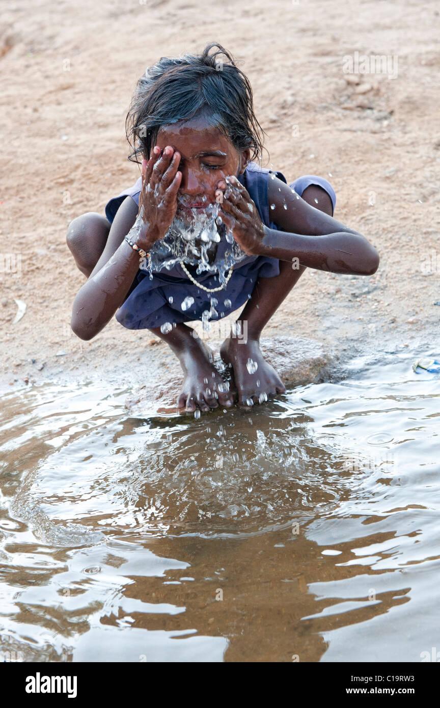 Pobre niña de la calle indio lavar su cara en un río en la India rural. En Andhra Pradesh, India Foto de stock