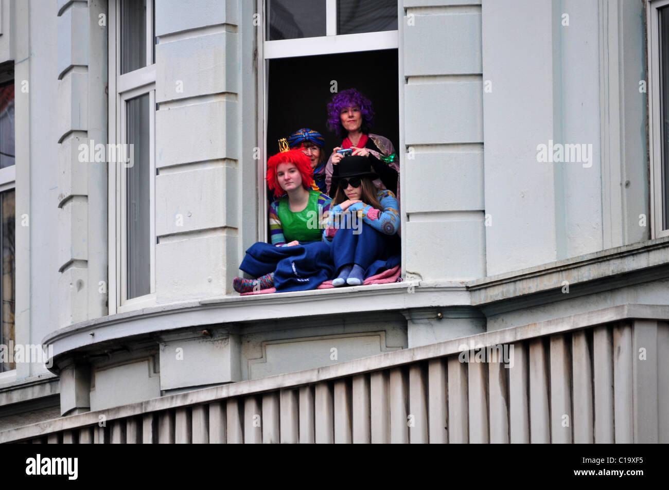 Cuatro personas en trajes de mirar hacia abajo en la calle, sentado ...