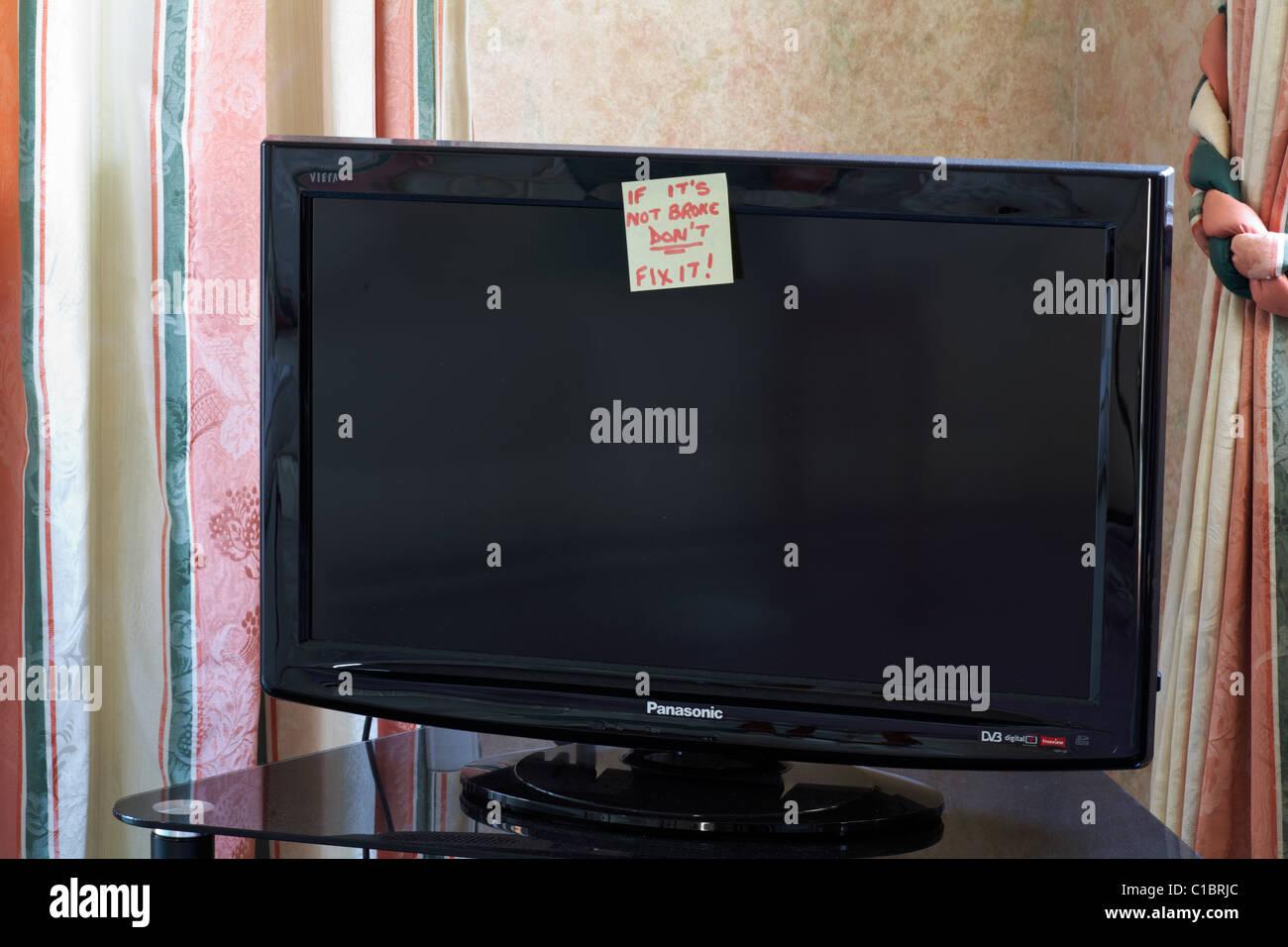 Si no está roto no lo arregle post nota pegada en la televisión en el salón Foto de stock