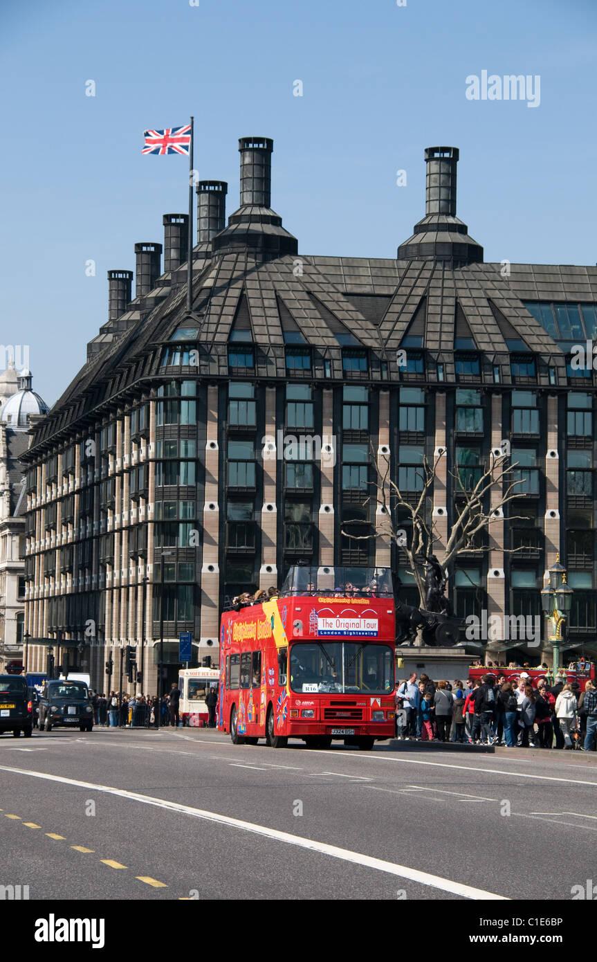 Una gira de Londres autobús pasa un grupo de turistas en el puente de Westminster. La union jack flag archivos anteriores Portcullis House. Foto de stock