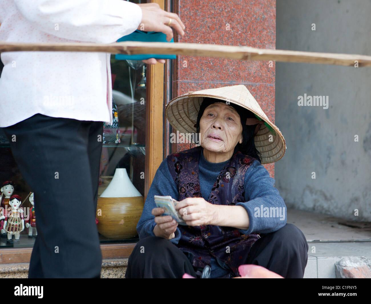 Retrato de la calle vieja en un sombrero cónico de la tradicional no en Hanoi, Vietnam Foto de stock