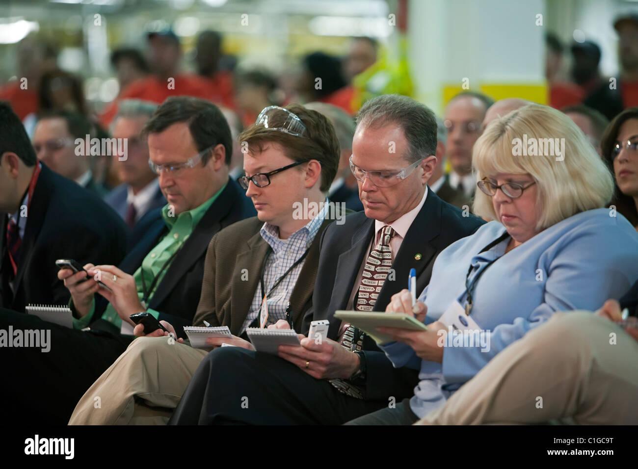 Los reporteros tomar notas durante los discursos de los funcionarios del sindicato y de la empresa en un evento Foto de stock