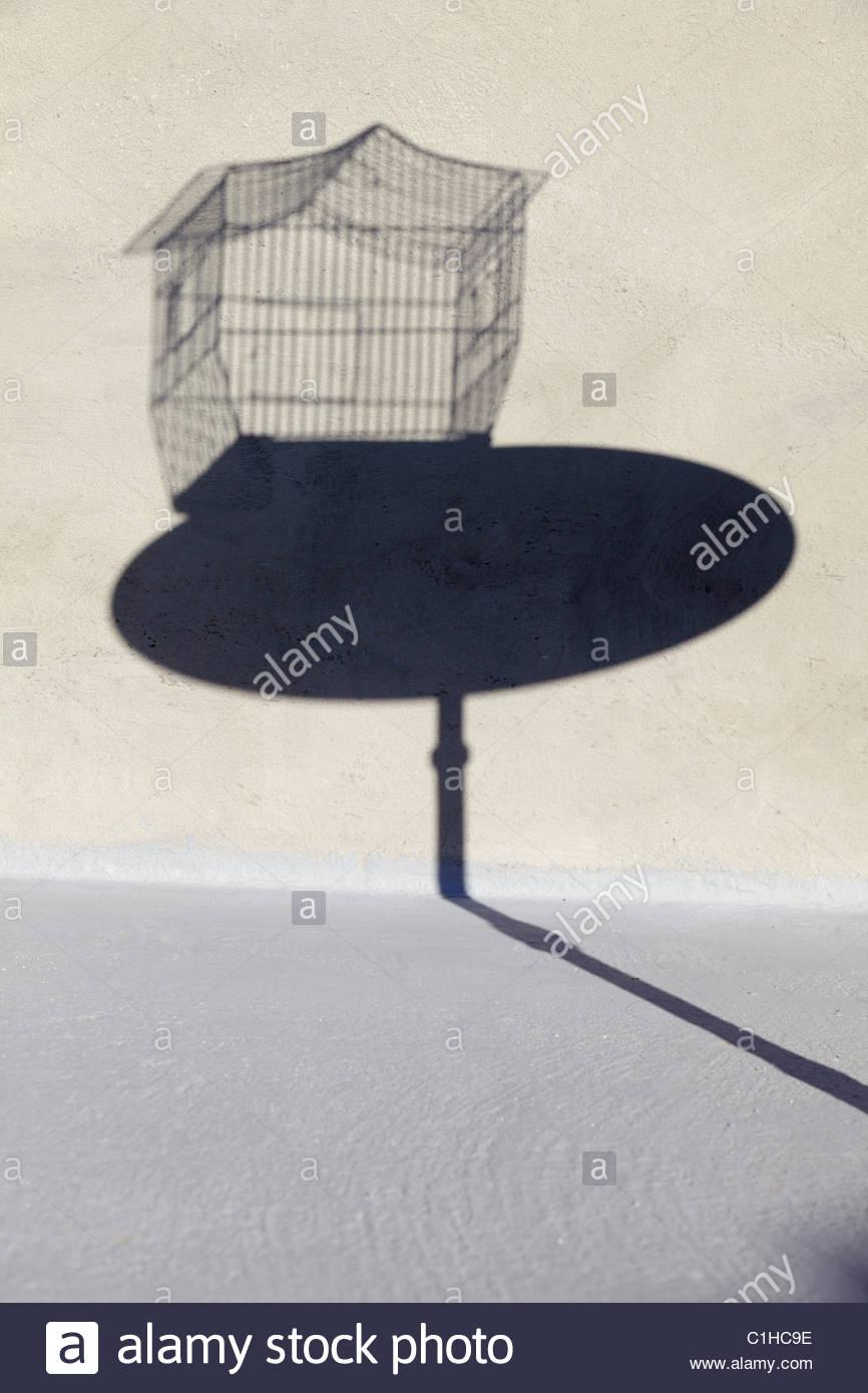 Sombra de forma de jaula vacía sobre una pequeña mesa redonda Imagen De Stock