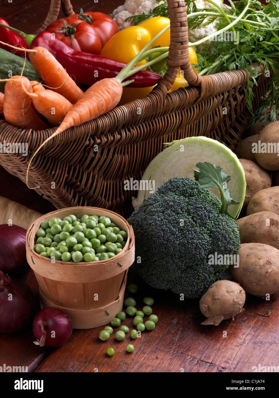 Cesta de mimbre de verduras crudas Tomates Zanahorias pimiento amarillo rojo dulce guisantes coliflor brócoli Imagen De Stock