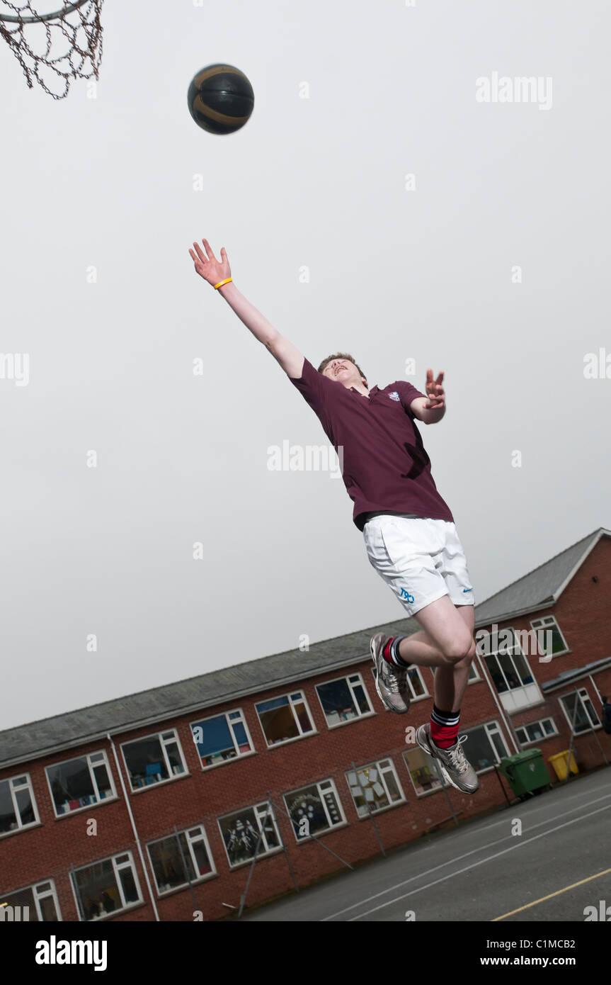 Un niño que jugaba baloncesto colegial de adolescentes en una escuela secundaria UK Imagen De Stock