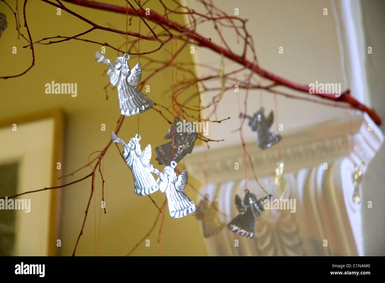 Tin angel decoraciones de navidad colgando de una rama Imagen De Stock