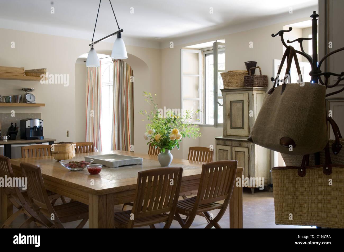 Mesa de comedor de madera y sillas plegables en cocina provenzal con ...