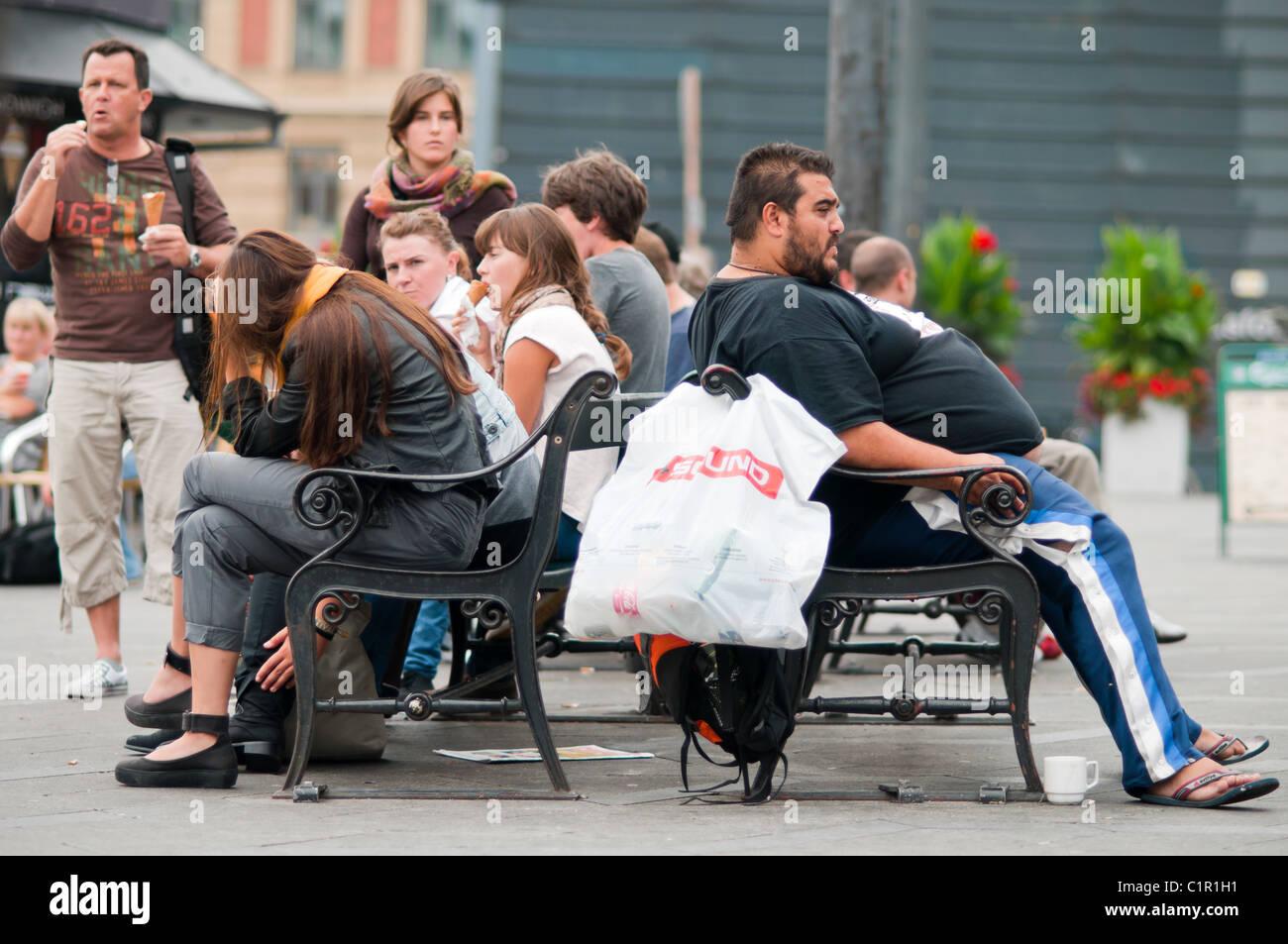 Extremadamente fat man descansa sobre un banco de trabajo. Slim adolescentes en el otro lado Imagen De Stock