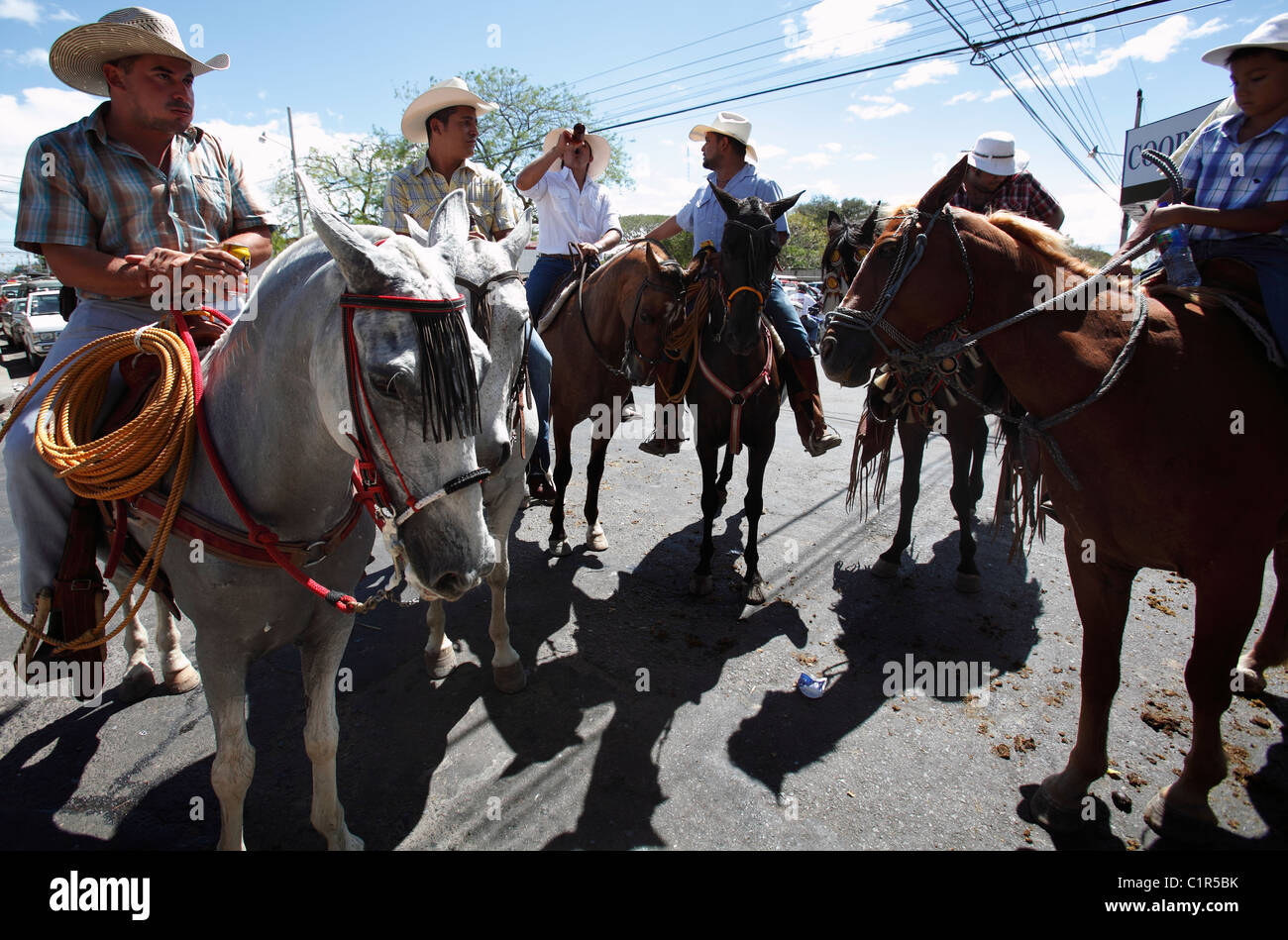 a8e650422 Los hombres de Costa Rica sobre caballos beber cerveza después de  participar en un desfile de