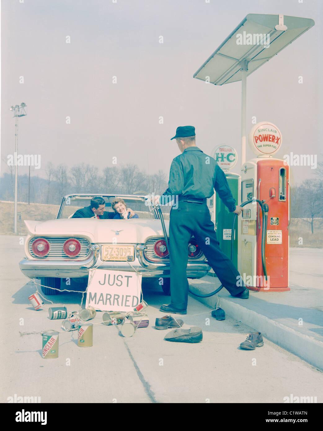 La pareja recién casada con signo de conducción a través de gasolinera Imagen De Stock