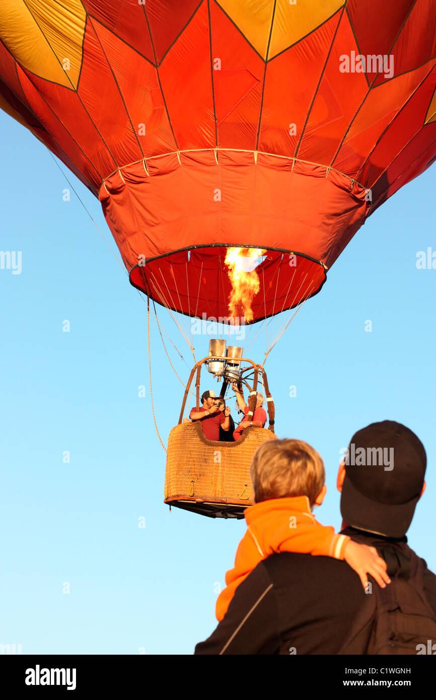 California, Estados Unidos, Ripon, espectadores viendo el despegue de globos de aire caliente en el cielo de color Imagen De Stock