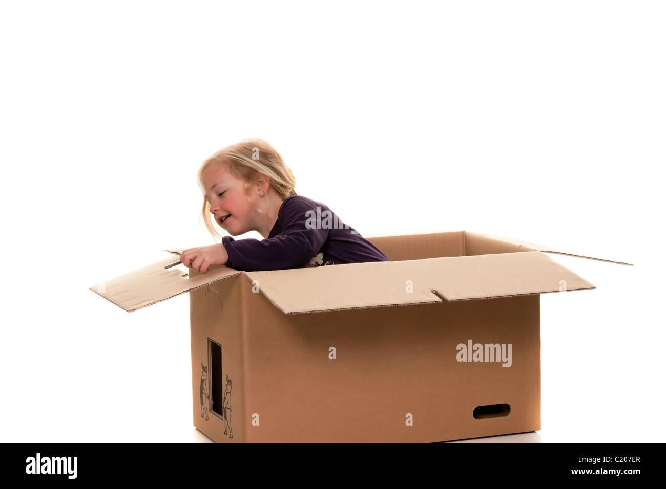 Niño en caja de cartón. Se está moviendo a la caja. Foto de stock