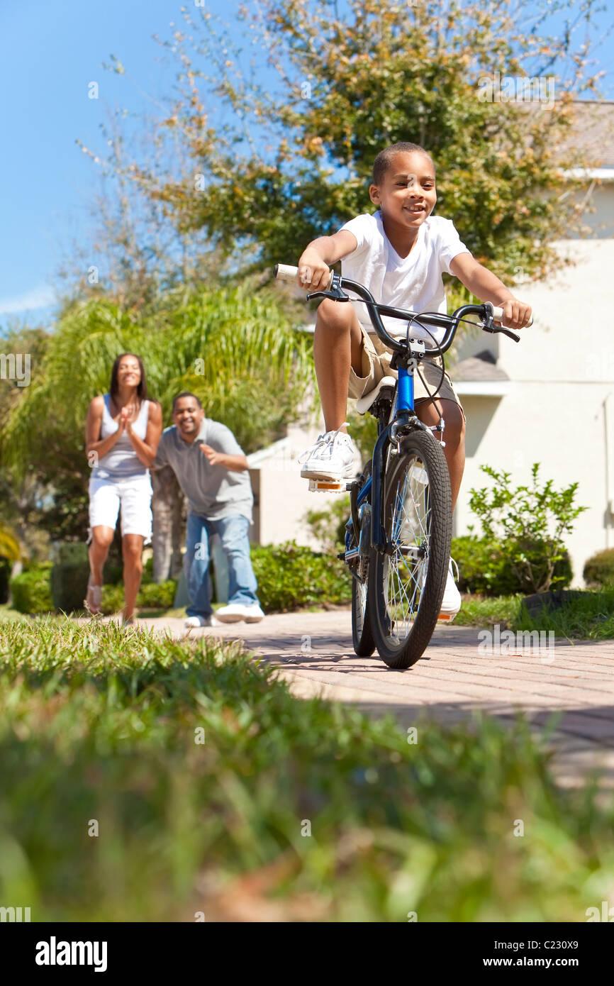 Una joven familia americana africana con el niño monta su bicicleta y su feliz emocionados padres dando aliento Imagen De Stock