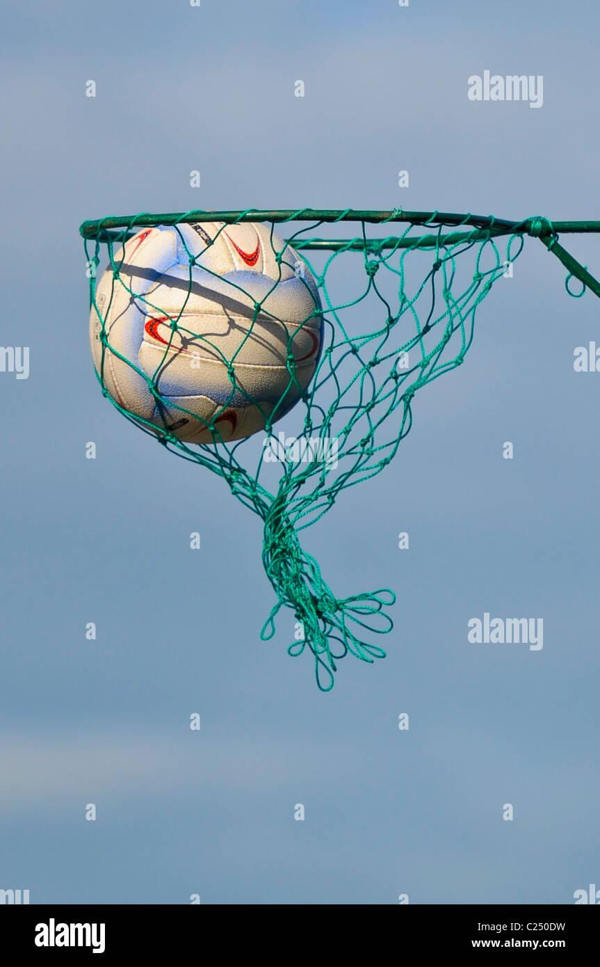 De cerca una netball pasando a través de una red.El cielo azul de fondo. Imagen De Stock
