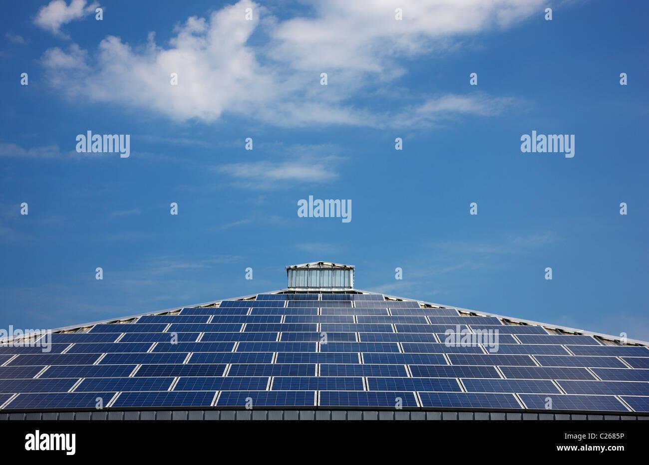 El techo de un edificio con paneles de energía solar. El cielo azul, el diseño de la pirámide. Alemania. Imagen De Stock