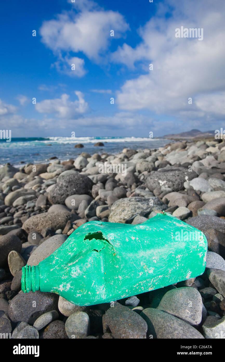 Una botella de aceite viejo acostado en una orilla rocosa. Bonita foto para entorno biodegradables o conceptos. Imagen De Stock