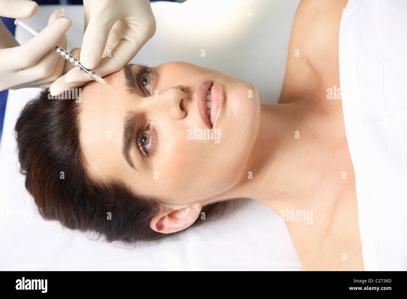 La mujer que recibe la inyección de Botox en la frente Foto de stock