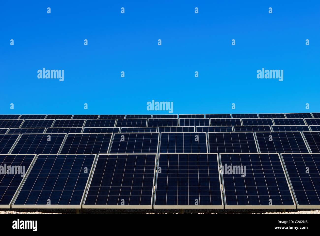Panel solar azul y blanco en una fila bajo el cielo azul claro Imagen De Stock