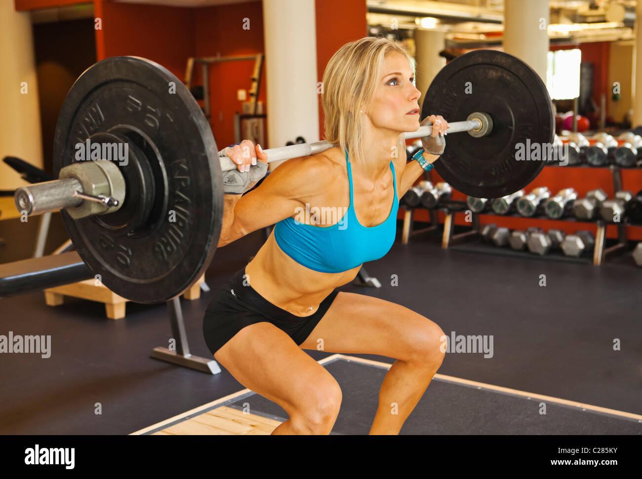 Una mujer físicamente apto hacer sentadillas en un club de la salud sala de pesas. Foto de stock