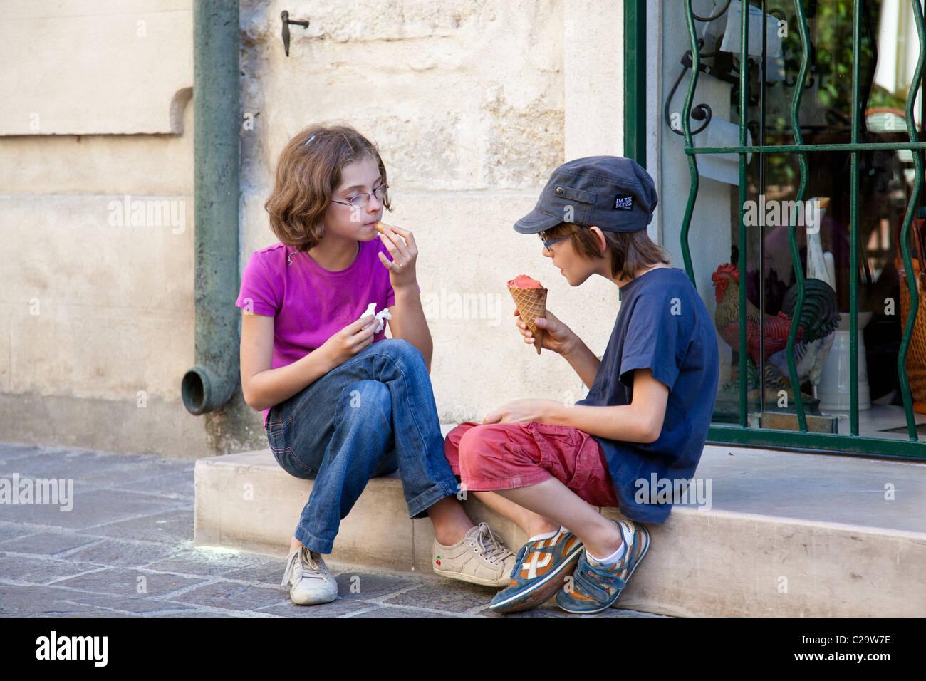 Los niños disfrutan de sus dos helados mientras estábamos sentados en algunos pasos de fabricación Imagen De Stock