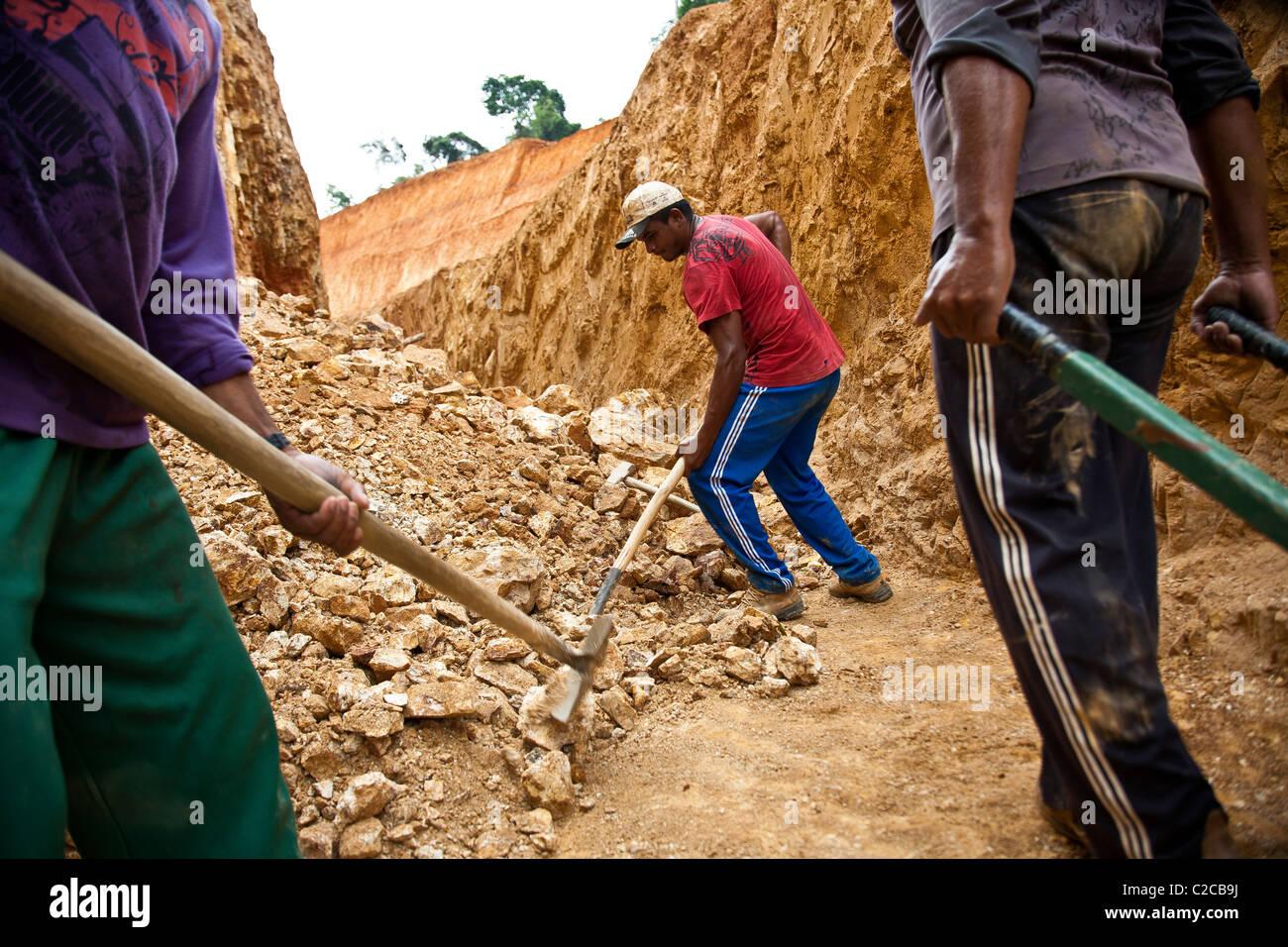 La prospección de yacimientos de oro de hardrock Amazon examen de superficie de los afloramientos rocosos, buscando exposiciones de vetas de minerales Foto de stock