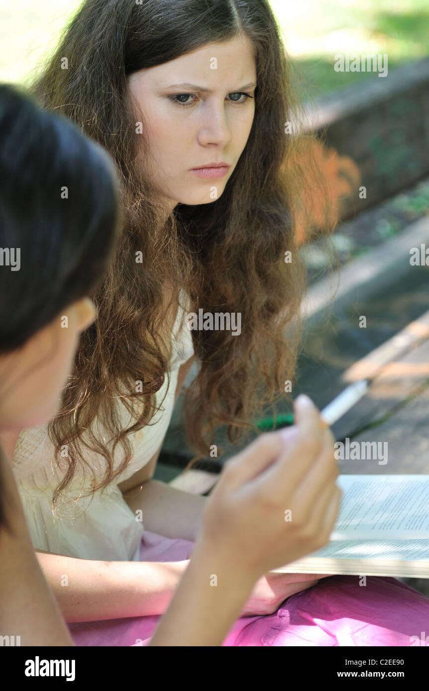 La cultura de la juventud - dos jóvenes al aire libre, una mujer fumar cigarrillo y molesta iritates otra chica Imagen De Stock