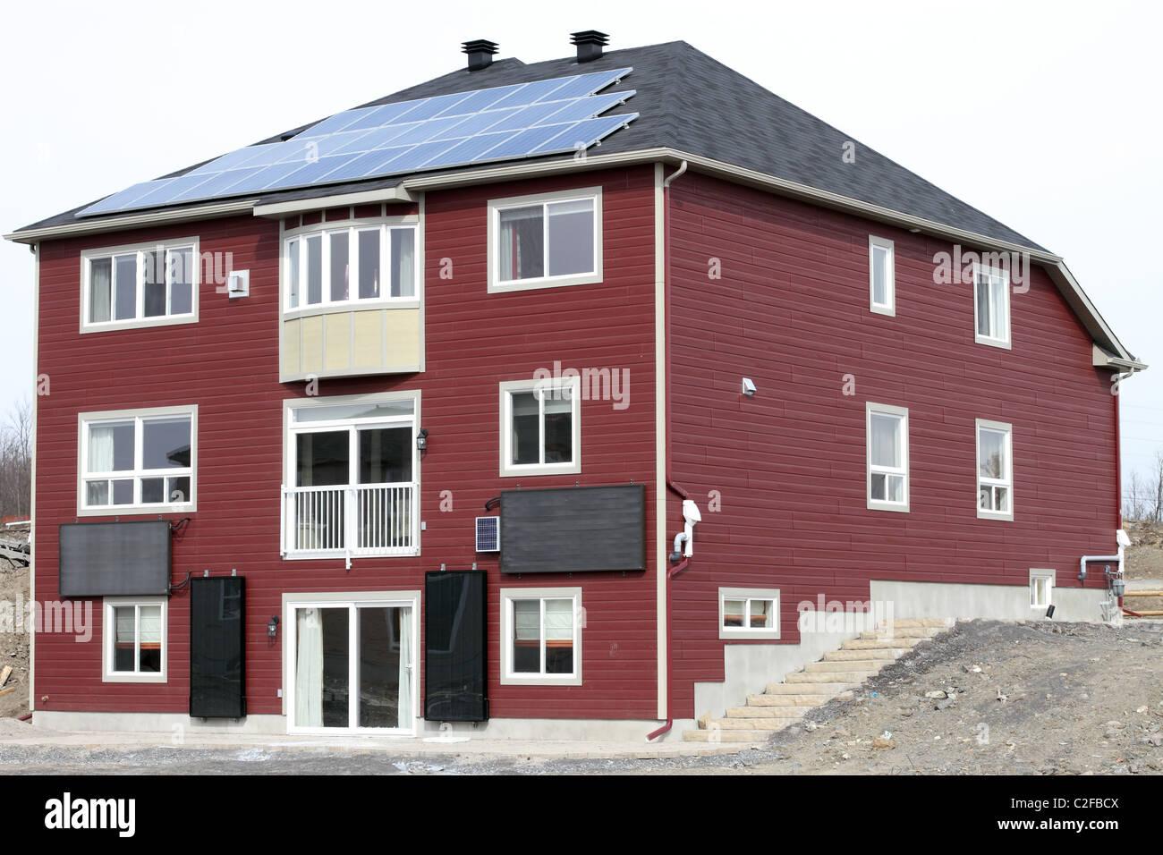 Casa nueva exhibición de energía verde con paneles solares en el techo y los calentadores de agua solares Imagen De Stock