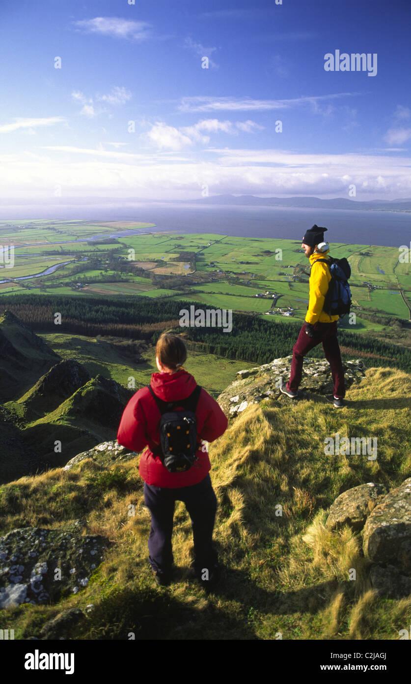 Caminantes mirando por encima de Magilligan punto desde la cumbre de Binevenagh, Condado de Derry, Irlanda del Norte. Imagen De Stock
