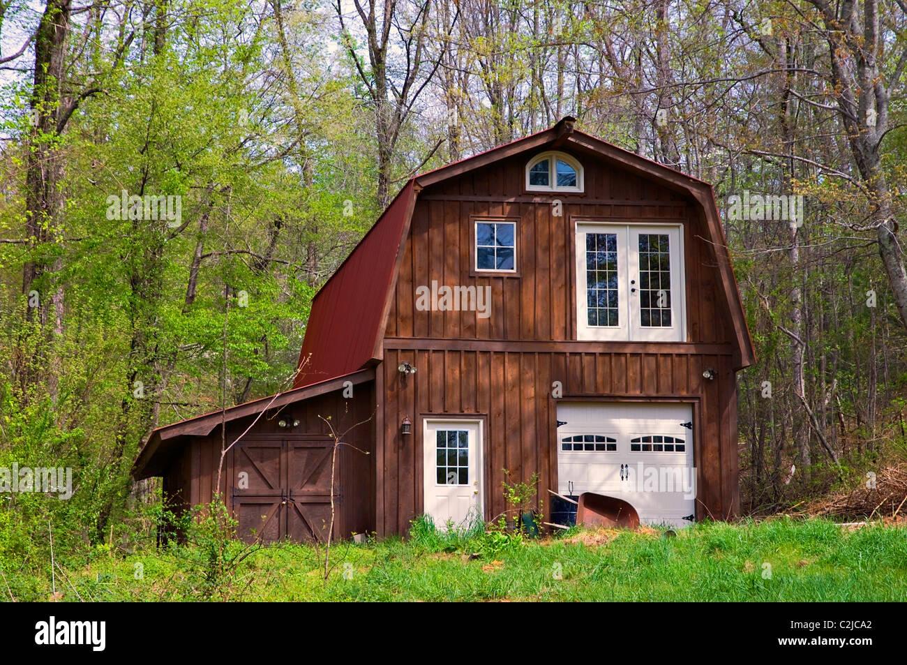 Un gran granero de madera con techo de metal rojo diseñado para ser usado como una residencia (si es necesario). Imagen De Stock