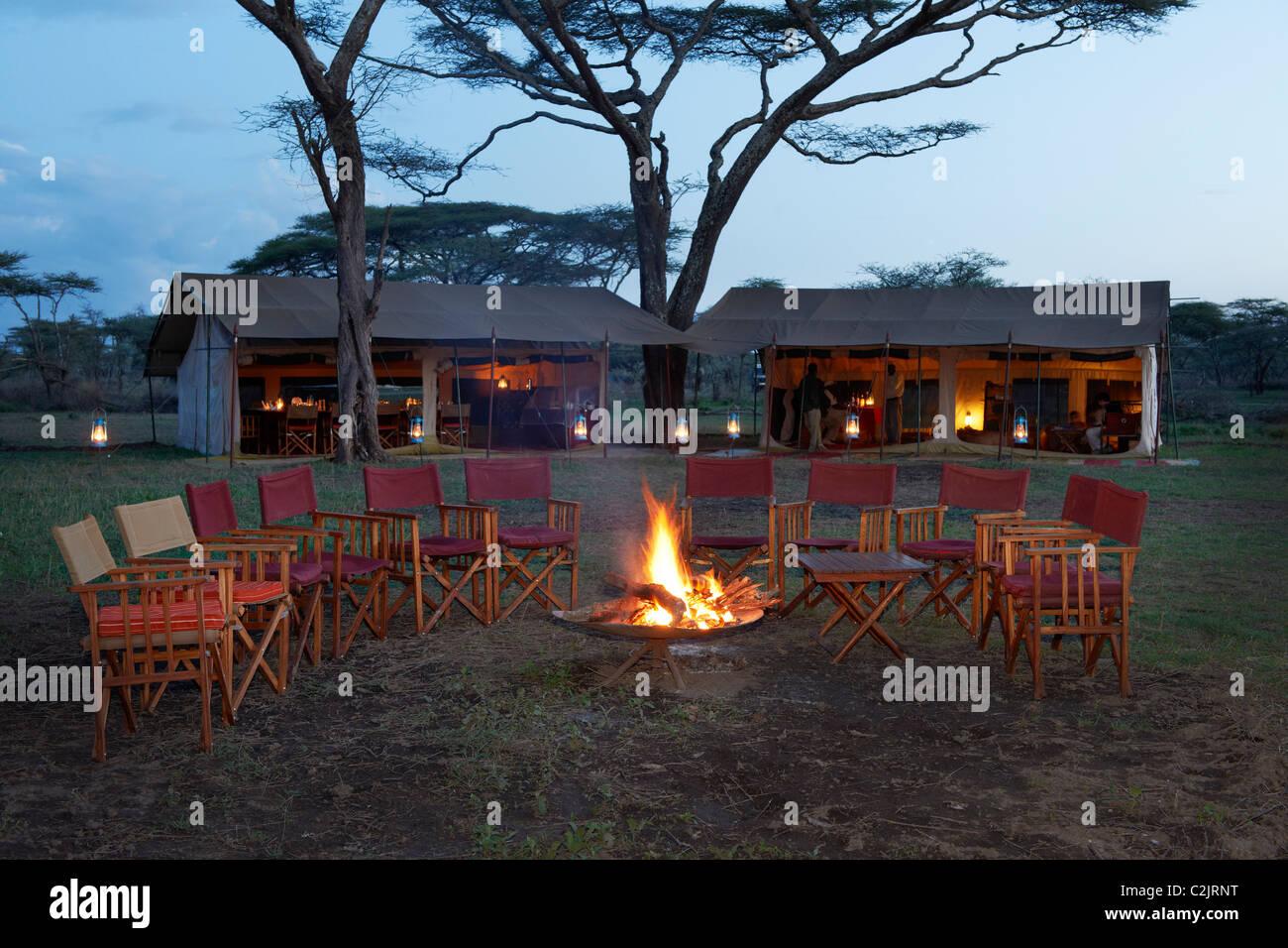 Sillas alrededor de la fogata, la carpa principal bajo el árbol del Serengeti Safari tendían Campamento Imagen De Stock