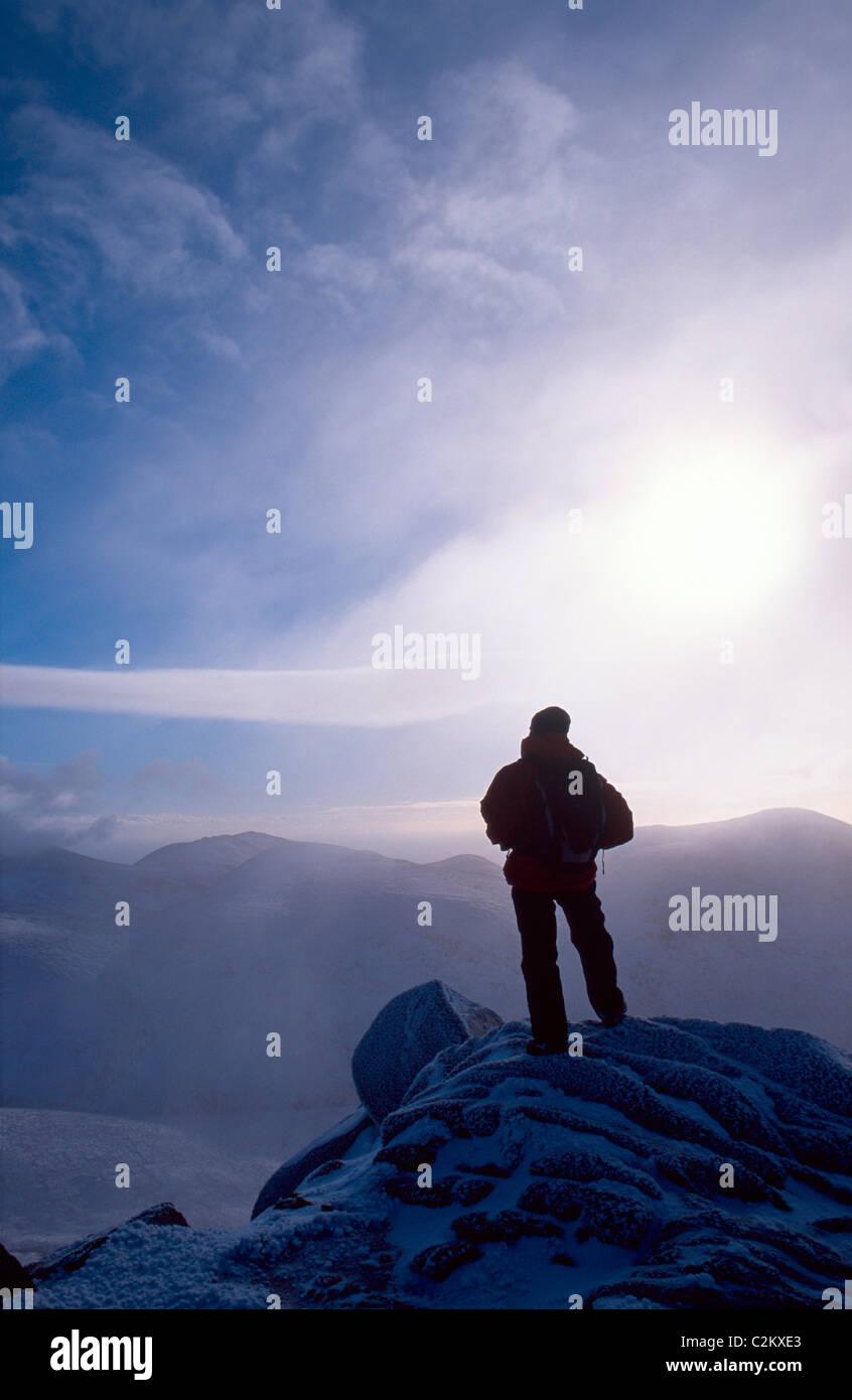 Walker en invierno la cumbre de Slieve Bearnagh, las Montañas Mourne, Condado de Down, Irlanda del Norte. Imagen De Stock