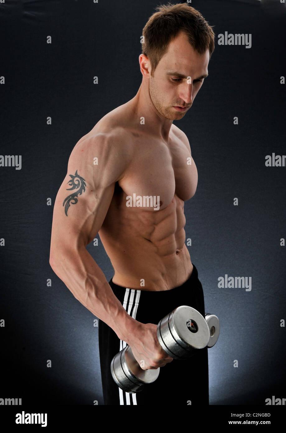 Fuerte guapo culturista levantando pesas para mejorar sus habilidades de capacitación para construir masculinidad Imagen De Stock