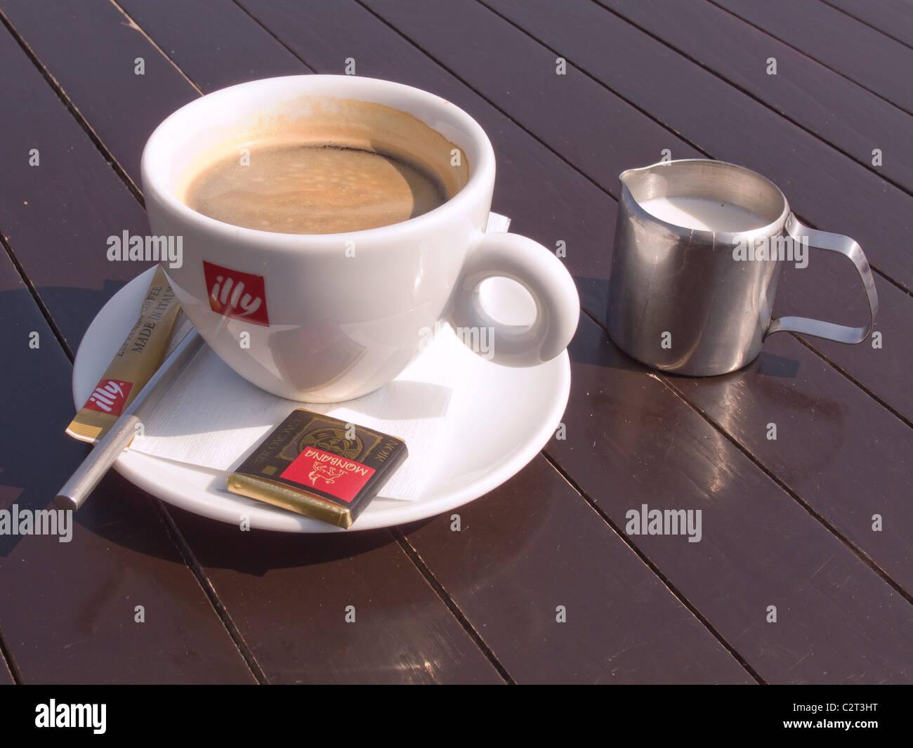 Una taza de café americano en una terraza exterior con una mesa de café Imagen De Stock