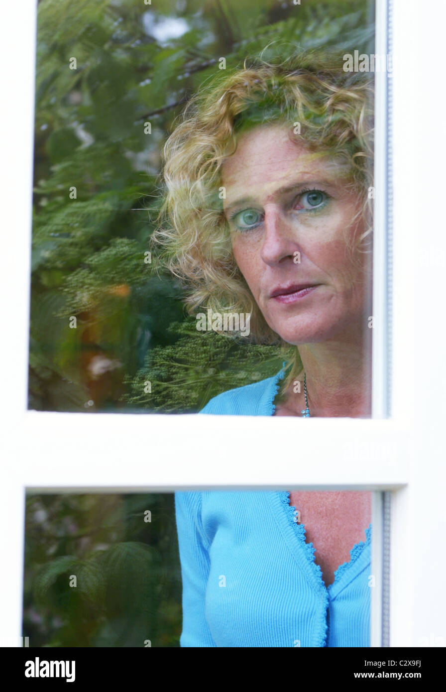 Solitaria, sospechosa o miedo adulto mirando hacia afuera de la ventana Foto de stock