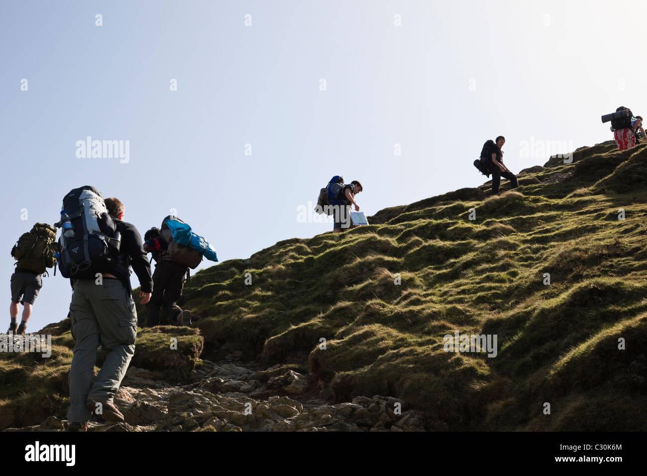 Los jóvenes mochileros subiendo por el Duque de Edimburgo premios subiendo Catbells Ridge en Lake District Imagen De Stock