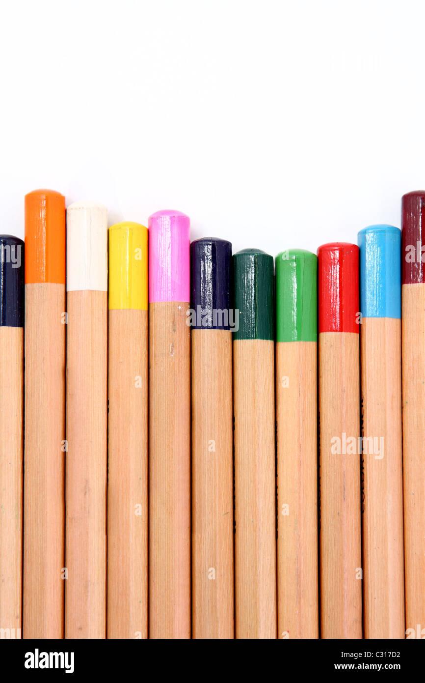Lápices de colores sobre un fondo blanco aislado de cerca . Imagen De Stock