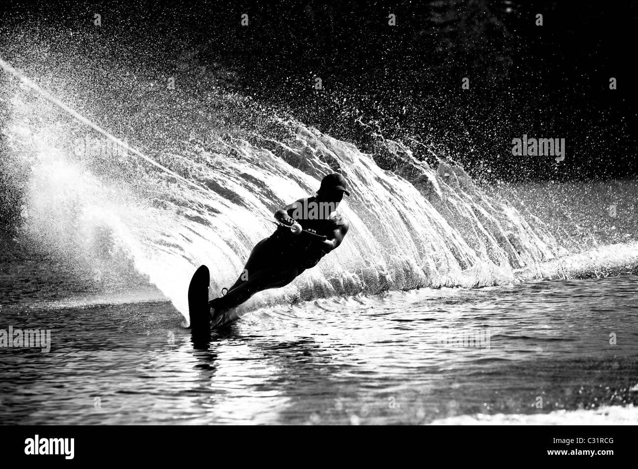Un esquiador de agua hembra rips un giro causando un enorme chorro de agua mientras esquía sobre Cobbosseecontee Imagen De Stock