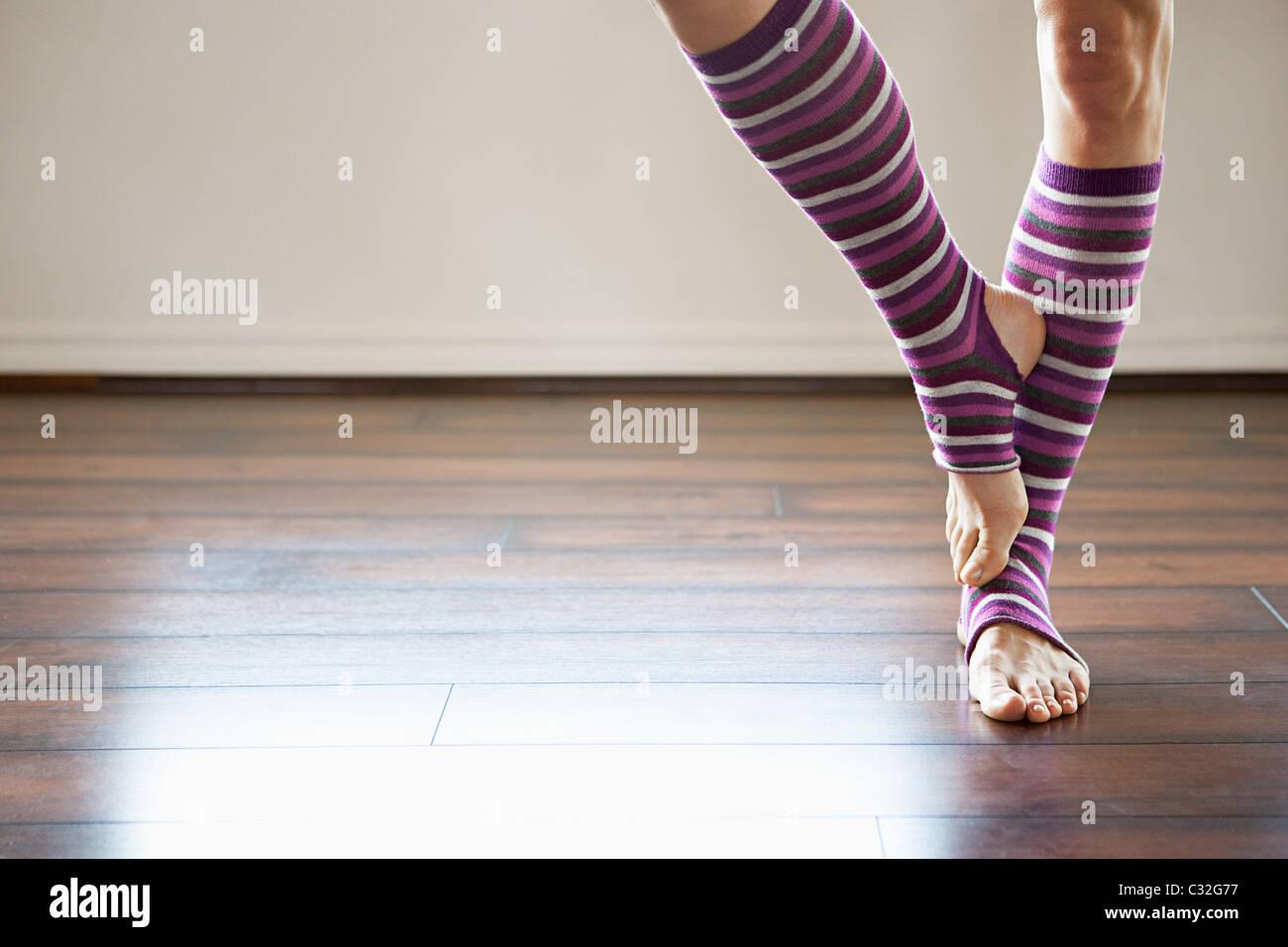 Mujer vistiendo stripey legwarmers de pie sobre una pierna. Imagen De Stock