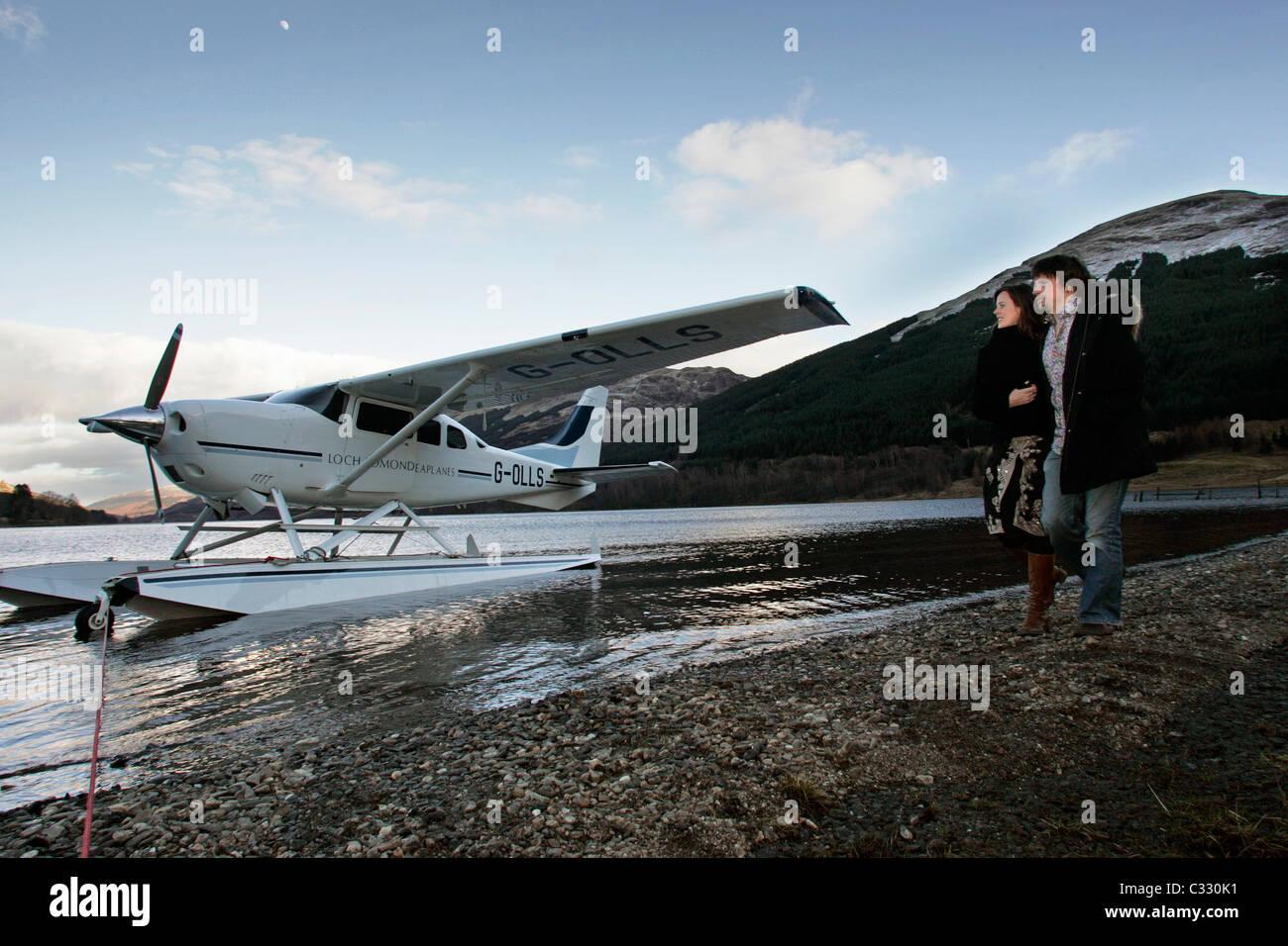 Una joven pareja en un viaje de un día a Loch Voil caminar a lo largo de la orilla pasando el hidroavión Imagen De Stock